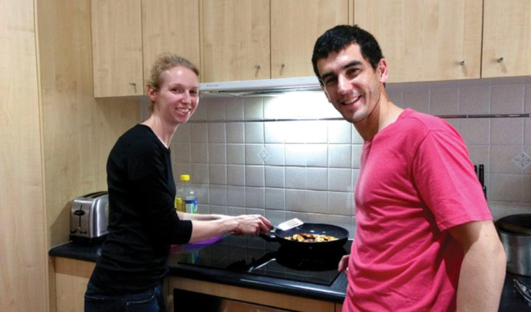 Two people cooking on electric stove