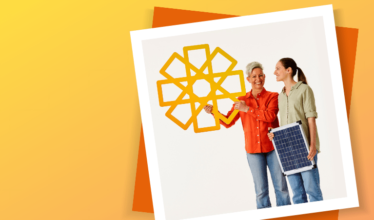 Two women holding a yellow cardboard sun and solar panel