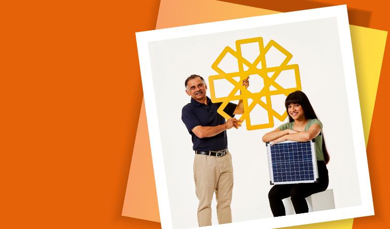 Man holding yellow cardboard sun and woman holding solar panels
