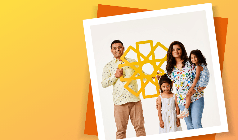Young family holding yellow cardboard sun