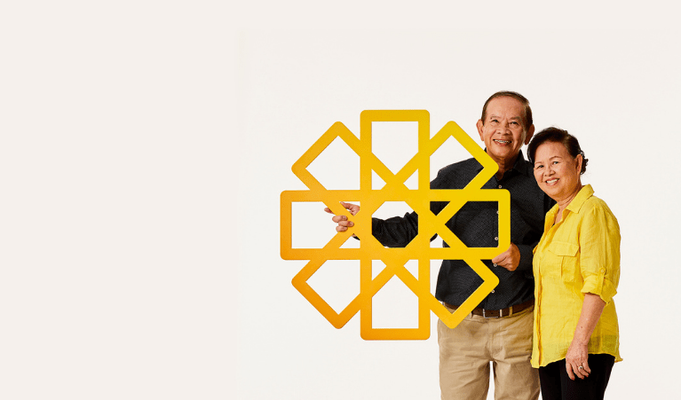 Family standing together, holding yellow cardboard sun