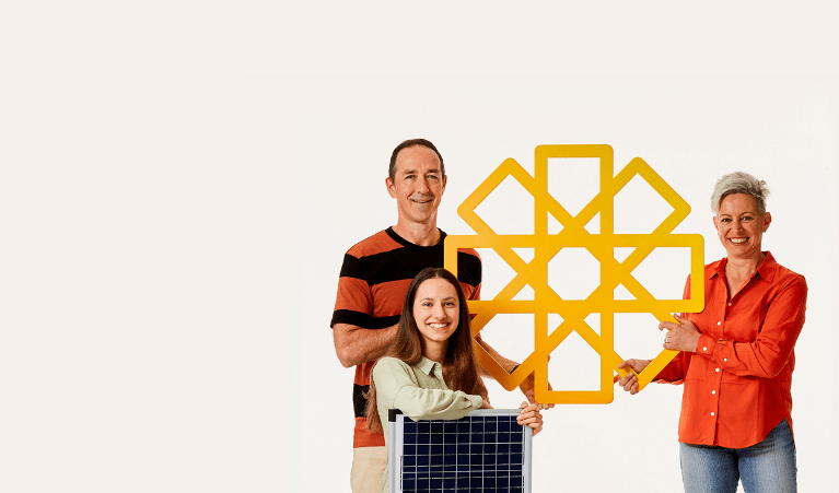 Family holding solar panel and cardboard yellow sun