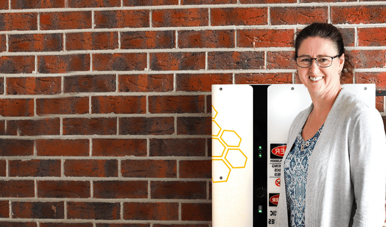Smiling woman standing in front of a brick wall and a solar battery