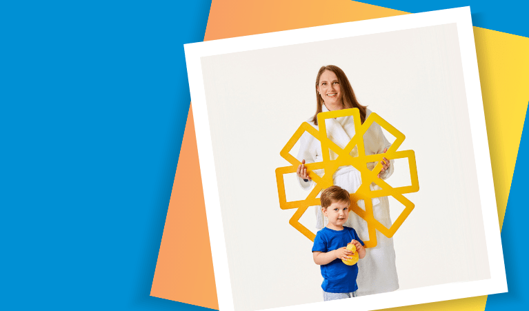 Woman and son dressed in blue, holding yellow cardboard sun and rubber duck