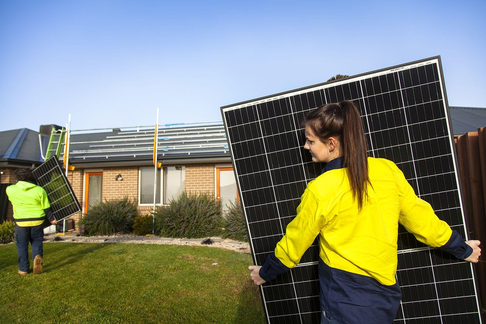 A woman in a high vis jumper carrying a solar panel