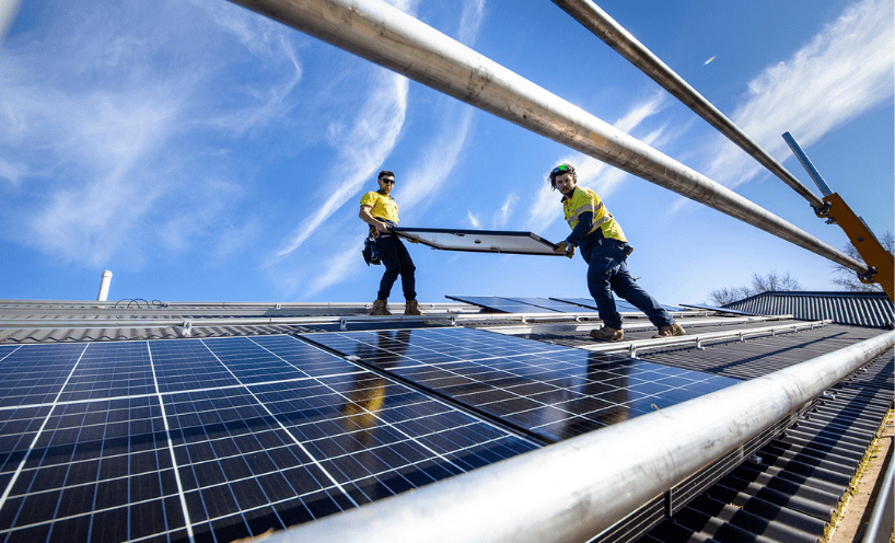 Two solar installers carrying a solar panel on a roof, with guard rails up