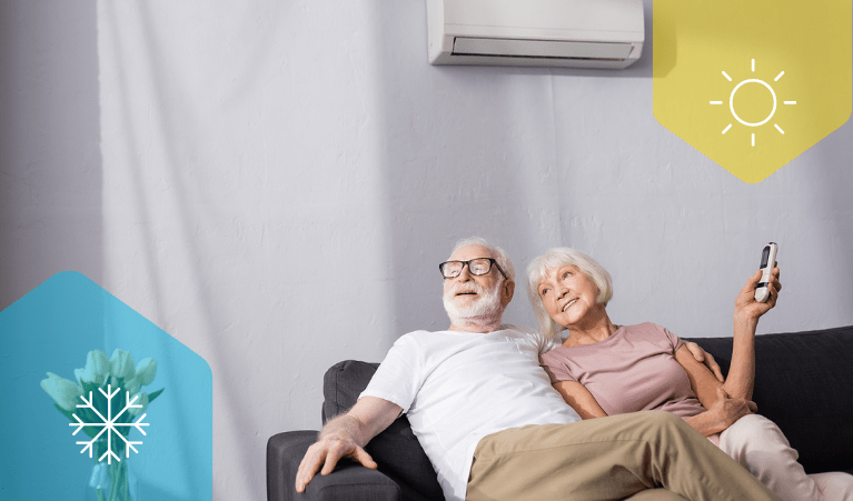 A couple sitting on a navy couch beneath a split system heating and cooling unit